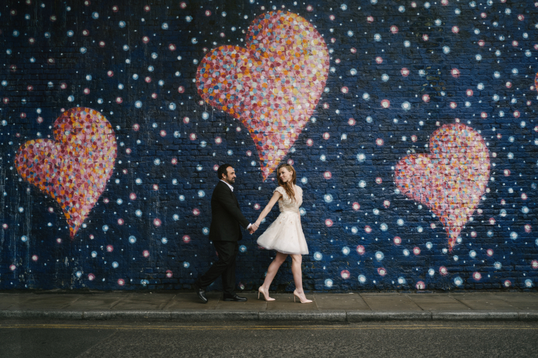 Couple walking past romantic street art for their wedding photoshoot in London
