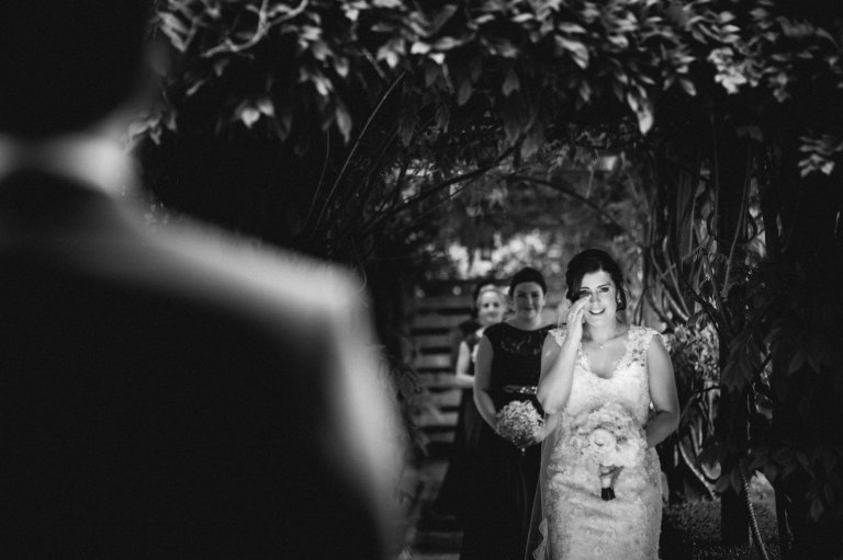 bride wipes tear from her eye as she walks down an aisle