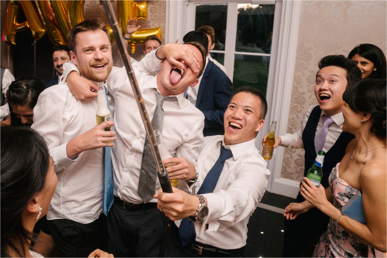 friends having fun with a selfie stick on the dance floor