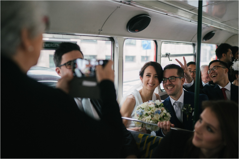 bride and groom pose for a picture when their guest photobombs them