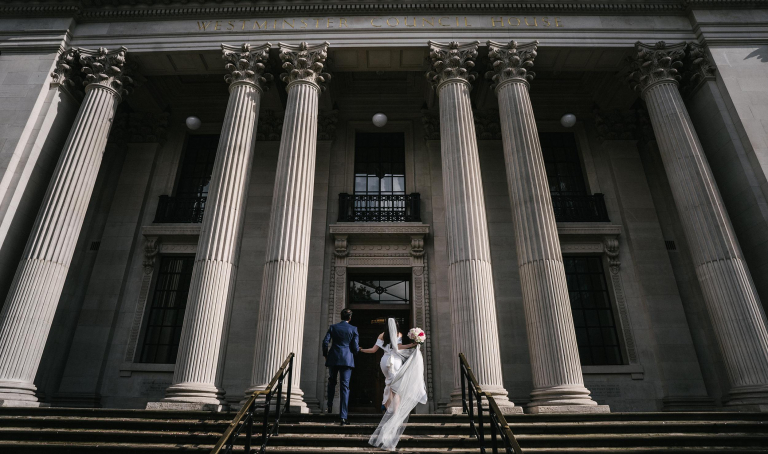 a wedding couple walking up marlyebone town hall and registry office to get married