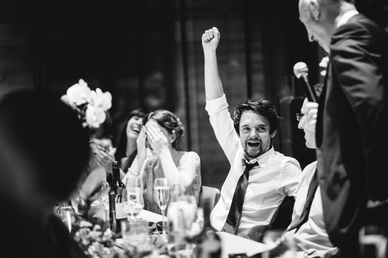 groom cheering during wedding speech